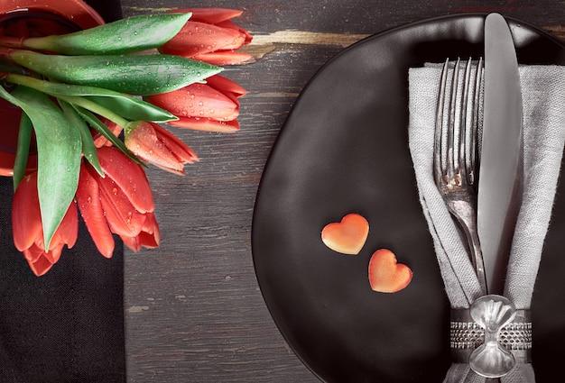 Zwarte borden, zwarte servetten, vintage bestek met rode tulpen en decoratieve harten