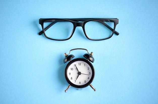 Zwarte bril en wekker op blauwe ondergrond.