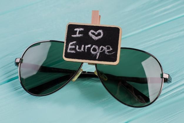 Zwarte bril op een houten ondergrond. ik hou van europa geschreven op het naamplaatje in de buurt van een zonnebril.