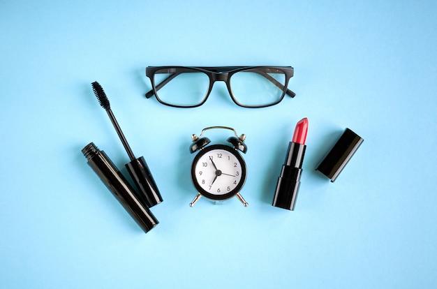 Zwarte bril, wekker, mascara en rode pommade op blauwe ondergrond.