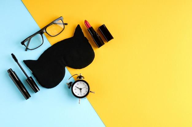 Zwarte bril, wekker, mascara, pommade en slaapmasker op blauwe en gele ondergrond.