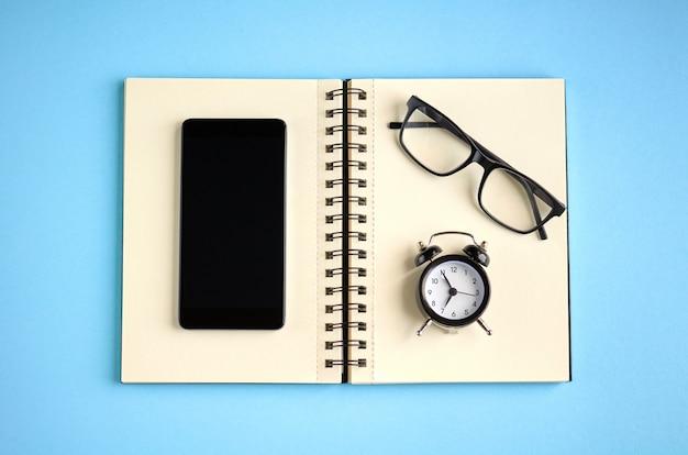 Zwarte bril, wekker, papieren notitieblok en mobiele telefoon op blauwe ondergrond.