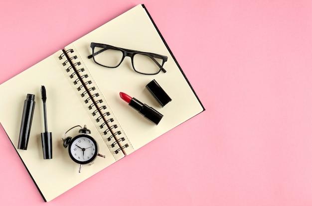 Zwarte bril, wekker, papieren notitieblok, mascara en rode pommade op roze oppervlak.