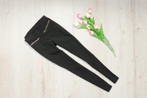 Zwarte broek en boeket tulpen. in de mode