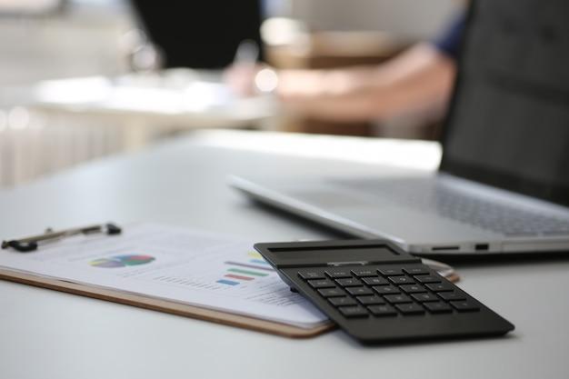 Zwarte calculator en financiële statistieken op klembordstootkussen