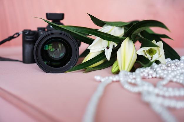 Zwarte camera met een lens en witte lelies en een parelsnoer op een roze achtergrond. selectieve aandacht. geen zichtbare logo's en merken