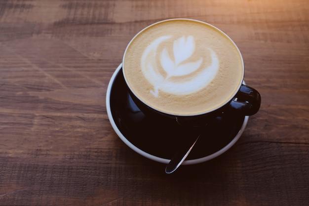 Zwarte cappuccino-kop op houten lijst in koffie.