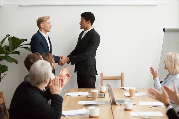 Zwarte ceo en witte zakenman handen schudden op groepsbijeenkomst