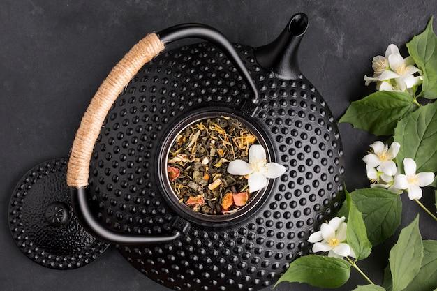 Zwarte ceramische theepot met droog kruidingrediënt en wit bloemtakje op zwarte achtergrond