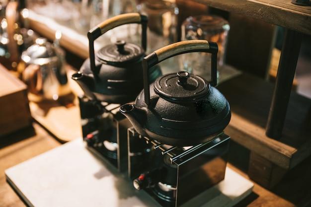 Zwarte ceramische waterkokers met houten handvat op fornuis voor het maken van druppelkoffie.
