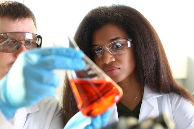 Zwarte chemicus vrouw en man analizing buis test in laboratorium