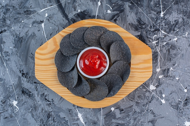 Zwarte chips en ketchup in houten plaat, op het marmeren oppervlak