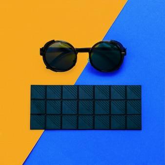 Zwarte chocolade en zonnebril steampunk. minimalisme details mode