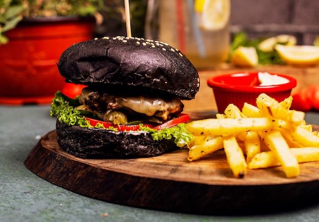 Zwarte chocolade pan rundvlees kaas hamburger met groenten fastfood, franse frietjes en ketchup.