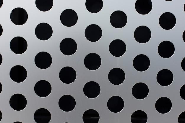 Zwarte cirkels op een metalen oppervlak textuur achtergrond