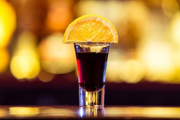 Zwarte cocktail in een stapel met een schijfje sinaasappel