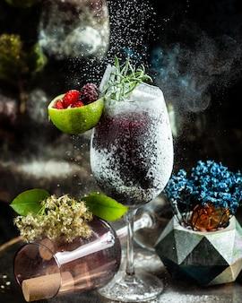 Zwarte cocktail met vanillepoeder en bessen.