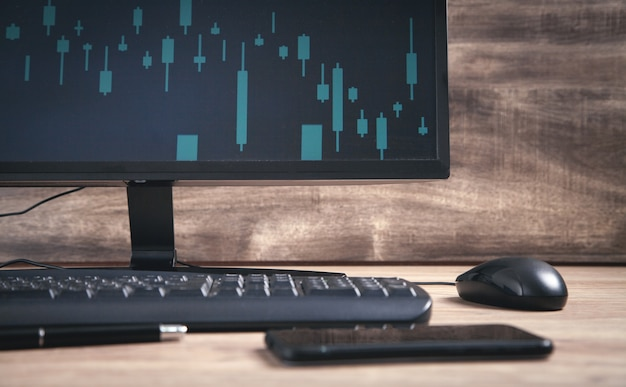 Zwarte computer met toetsenbord en muis op tafel. grafieken op het scherm. analyse. bedrijf