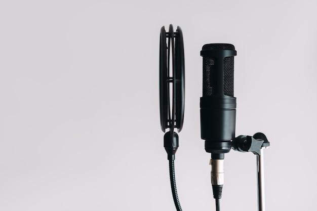 Zwarte condensatormicrofoon op statief met popfilter