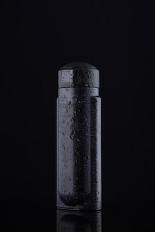 Zwarte container voor vloeistoffen en shampoo op een zwarte achtergrond