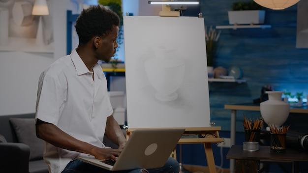 Zwarte creatieve kunstenaar met laptopcomputer in kunststudio