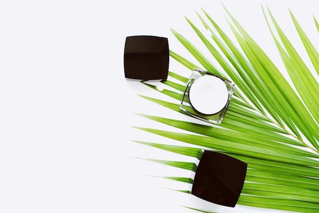 Zwarte crème fles geplaatst op groene bladeren.