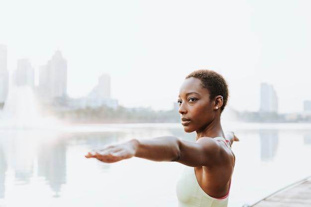 Zwarte dame doet een virabhadrasana-pose