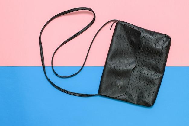 Zwarte damestas met riempje op roze en blauw