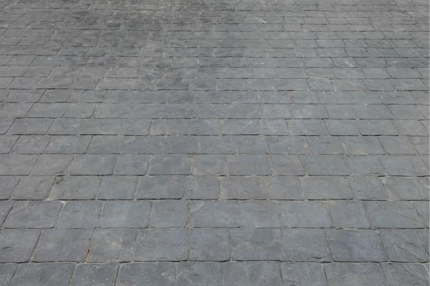 Zwarte de baksteenvloer van de close-upoppervlakte bij de achtergrond van de wegtextuur