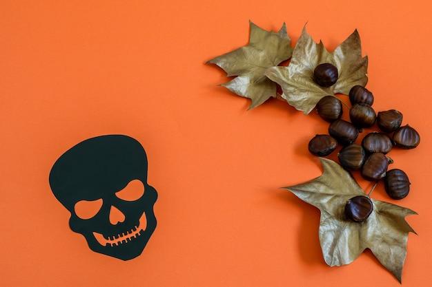 Zwarte decoratieve schedel en kastanjes met gouden bladeren op sinaasappel. plat leggen
