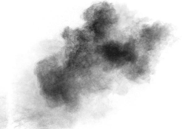 Zwarte deeltjes spetterde op een witte achtergrond. zwart poederstof spatten.
