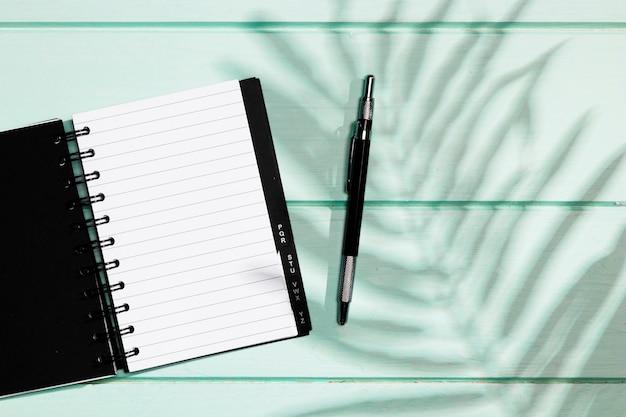 Zwarte dekking van notitieboekje met pen en bladerenschaduw
