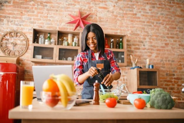 Zwarte die in schort gezond ontbijt kookt