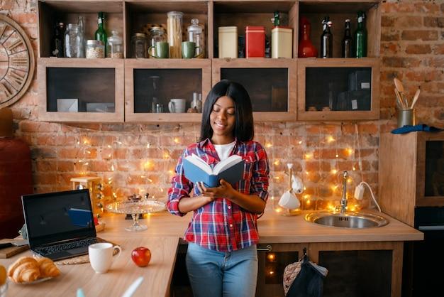 Zwarte die op zoek is naar receptenboek, jong etnisch meisje dat op de keuken kookt. afrikaanse vrouwelijke persoon voorbereiding van plantaardige salade thuis, gezonde levensstijl