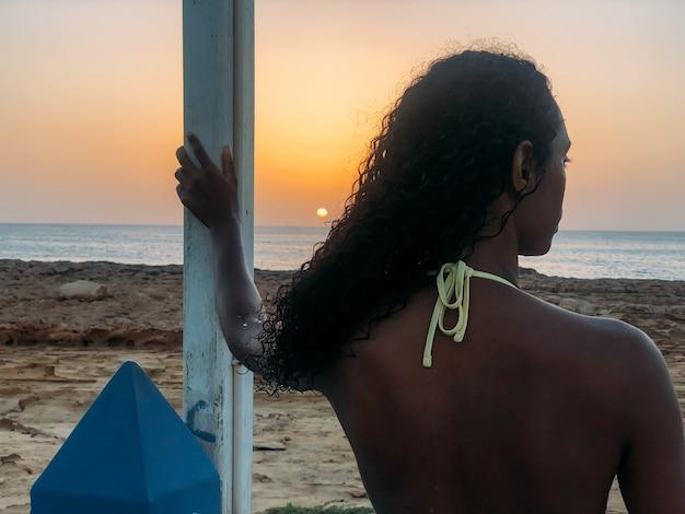 Zwarte die weg de zonsondergang op strand kijken