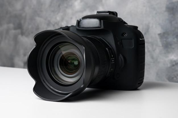 Zwarte digitale camera op een tafel met grunge achtergrond.