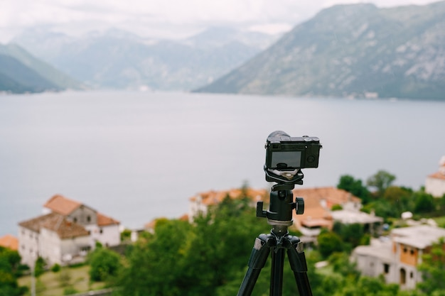 Zwarte digitale camera staat op een statief tegen het panorama van de stad en de bergen