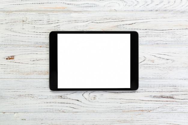 Zwarte digitale tablet op rustieke houten tafel, bovenaanzicht