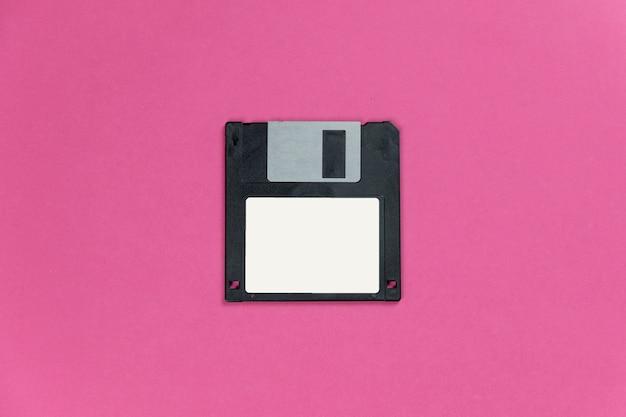 Zwarte diskette op roze achtergrond. retro magnetische opslag