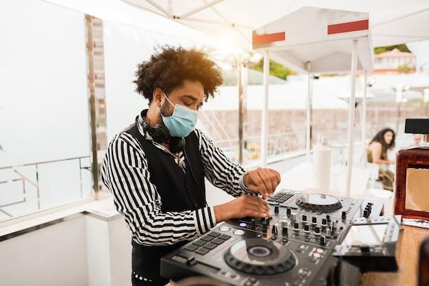 Zwarte dj die buiten muziek speelt in de cocktailbar terwijl hij een gezichtsmasker draagt