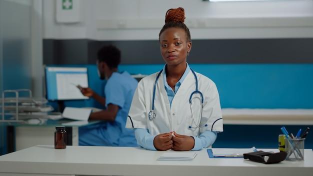 Zwarte dokter op videogesprek online conferentie zittend aan bureau in medische kast. afro-amerikaanse arts die communicatie op afstand op internet gebruikt voor telegeneeskunde die mensen behandelt