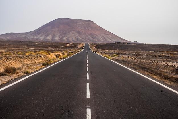 Zwarte donkere asfaltweg midden in de woestijn en zandduinen