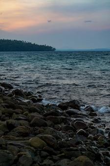 Zwarte donkere steen op het strand in de zee met een beetje slakken dat hele gebied. het is schemertijd in azië, thailand.