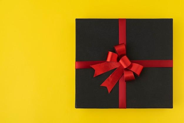 Zwarte doos met een rood lint en een strik op een felgele achtergrond. bovenaanzicht