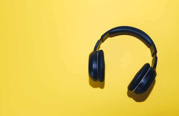 Zwarte draadloze hoofdtelefoon geïsoleerd op een gele achtergrond