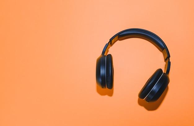 Zwarte draadloze hoofdtelefoon geïsoleerd op een oranje achtergrond