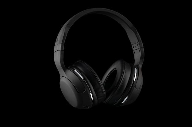 Zwarte draadloze hoofdtelefoons die op een zwarte achtergrond worden geïsoleerd.
