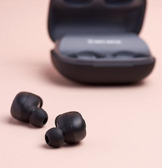 Zwarte draadloze kleine oortelefoons en een oplaaddoos