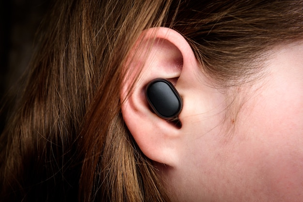 Zwarte draadloze koptelefoon in het oor.