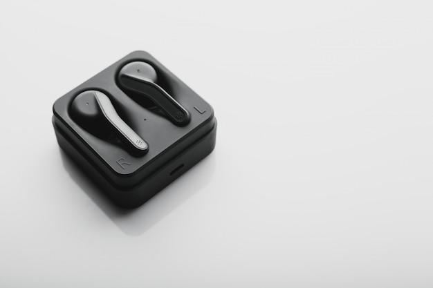 Zwarte draadloze oordopjes met powerbank case op een wit oppervlak